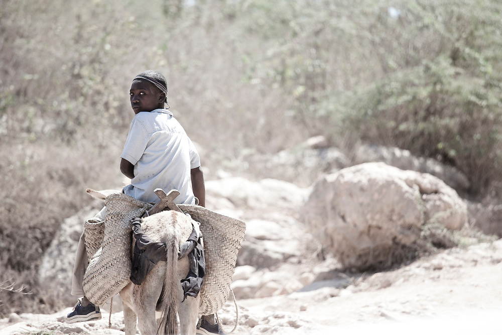 A girl riding a donkey glances back at the camera in ile de La Gonave, Haiti