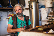Portrait of a man in a Raki distillery in Maza, a mountain village located close to Palaiochora which is a small town in Chania regional unit on the island of Crete, Greece.