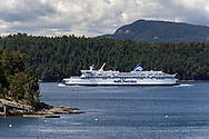 The BC Ferries vessel Spirit of British Columbia (built in 1993) navigates Trincomali Channel on the way to Victoria (Swartz Bay) from Tsawwassen.  Photographed from Village Bay on Mayne Island, British Columbia, Canada.  Island in the background is Prevost Island (front) and Salt Spring Island (Mount Tuam) behind.