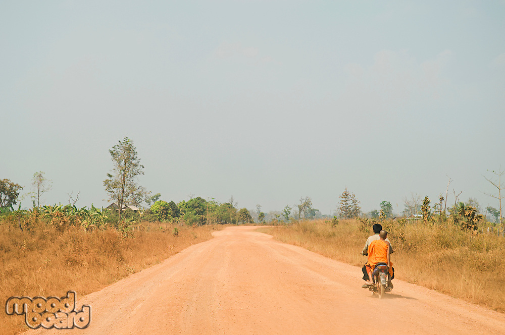 Motorcyclist Giving Ride to Young Monk on Rural Road
