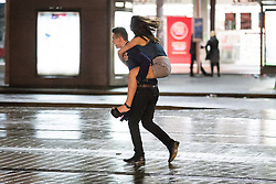© Licensed to London News Pictures . 01/01/2015 . Manchester , UK . A man gives a piggy back ride to a woman in Piccadilly Gardens . Revellers usher in the New Year on a night out in Manchester City Centre .  Photo credit : Joel Goodman/LNP