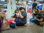 20 AUGUST 2015  - BANGKOK, THAILAND: People pray at the funeral for Yutnarong Singraw Thursday. More than 100 people gathered at Wat Bang Na Nok in Bangkok for the third day of the funeral rites for  Yutnarong Singraw, a Thai man who was killed in the bombing at the Erawan Shrine in Bangkok Monday. Yutnarong was delivering legal documents when the blast occurred. More than 20 people were killed and more than 100 injured in the blast.      PHOTO BY JACK KURTZ