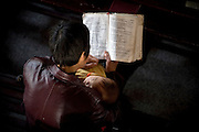 A Chinese christian holds a baby as she reads a bible during a service  in Pucheng, Shanxi.