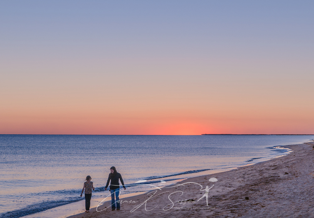 A mother and daughter walk along the west end of Dauphin Island at sunset. (Photo by Carmen K. Sisson/Cloudybright)