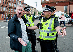 Pictured: A protester argues with police officers.<br /> <br /> Protesters gathered outside the main Home Office building in Glasgow to protest at private company SERCO's attempts to evict failed asylum seekers from their homes.<br /> <br /> © Dave Johnston / EEm