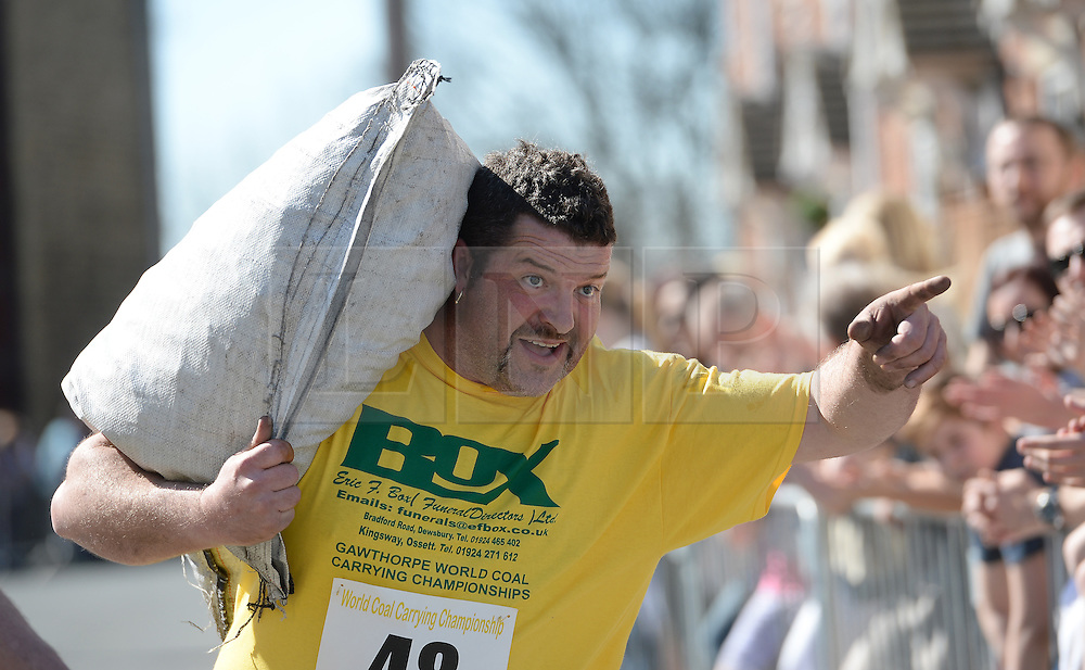 © Licensed to London News Pictures. 06/04/2015. Gawthorpe, UK. A competitor gestures as he approaches the finish line during the World Coal Carrying Championships, Gawthorpe, West Yorkshire. Photo credit : Anna Gowthorpe/LNP