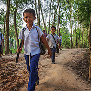 School kids heading home on the main road through Poom Prey, Cambodia. The road is all torn up thanks to large trucks that move factory workers to sweatshops near the Vietnamese border.