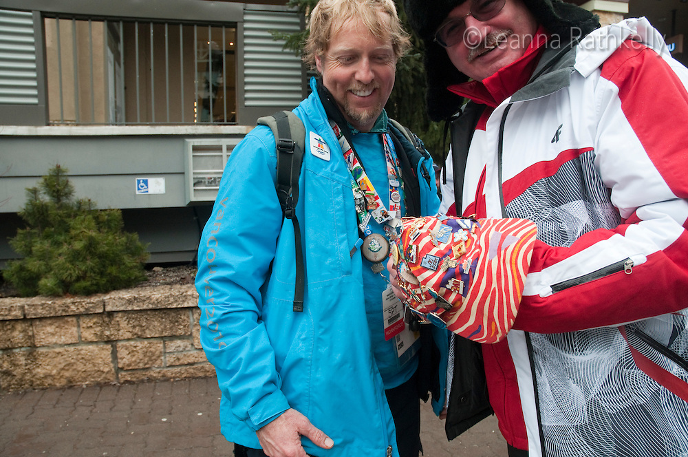Tom Jackson, Whistler local, trades pins with a man from Russia at the 2010 Olympic Winter Games in Whistler, BC Canada