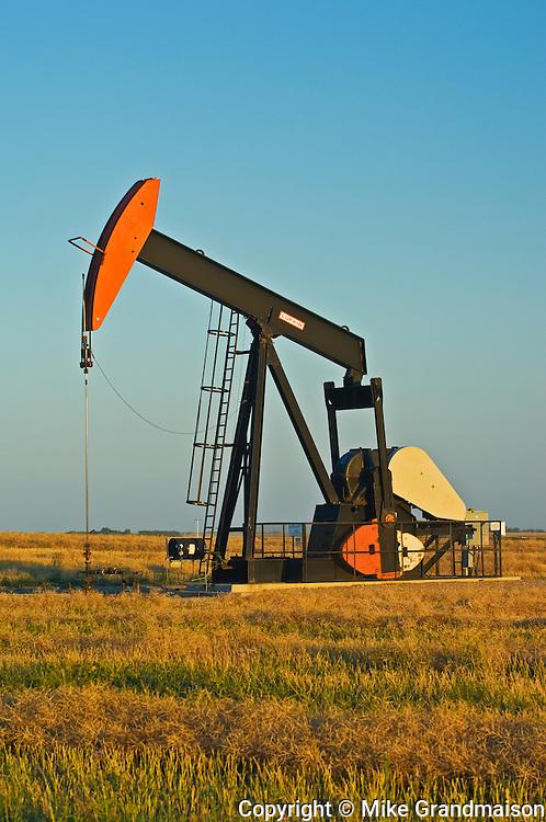 oil pump jack and canola field<br /> Carlyle<br /> Saskatchewan<br /> Canada