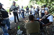 Jose Manuel Mireles, a surgeon coordinating self defense forces in Michoacan, talks to fighters and local leaders outside the town of Buenavista. Locals from at least a dozen towns have organized the groups to fight the brutal Knights Templar drug gang. The fighters include farmers, ranchers, loggers, and others who decided they'd finally had enough.