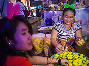 31 DECEMBER 2012 - BANGKOK, THAILAND:  Flower garland vendors in New Year's Eve hat make flower garlands for people going to a nearby Buddhist temple on New Year's Eve in Bangkok. The traditional Thai New Year is based on the lunar calender and is celebrated in April, but the Gregorian New Year is celebrated throughout the Kingdom, especially in larger cities and tourist centers, like Bangkok, Chiang Mai and Phuket. The Bangkok Countdown 2013 event was called ?Happiness is all Around @ Ratchaprasong.? All of the streets leading to Ratchaprasong Intersection were closed and the malls in the area stayed open throughout the evening.   PHOTO BY JACK KURTZ