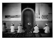Turpanlik men prayer in village mosque, Turpan Oasis, Chinese Turkestan.
