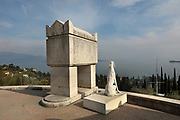 Tomb of a hero with dog sculpture by Velasco Vitali, at the Mausoleum, with the tomb of D'Annunzio, on the Mastio hill at Vittoriale degli italiani, or The Shrine of Italian Victories, the home, estate and museums of Gabriele D'Annunzio, 1863-1938, Italian writer, soldier and fascist, at Gardone Riviera, Lake Garda, Brescia, Lombardy, Italy. The funeral monument was designed by Gian Carlo Maroni after d'Annunzio's death, in the style of Etruscan-Roman grave sites, with 3 marble circles representing the victories of the Humble, the Sappers and the Heroes. At the centre is the tomb of d'Annunzio surrounded by 10 other heroes of Fiume including Guido Keller, Giuseppe Piffer, Ernesto Cabruna and Gian Carlo Maroni. In 2013 iron and cement dog sculptures by Velasco Vitali were added. Picture by Manuel Cohen