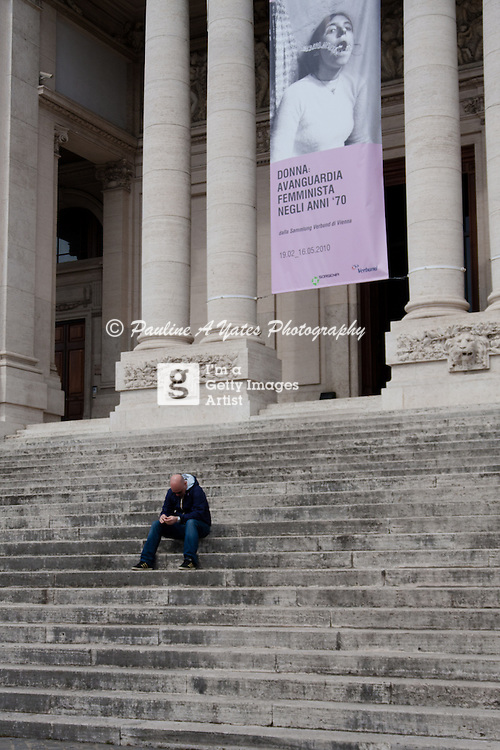 Taken on the steps of a museum in Rome. A lonely man, behind him an advertisement for a display on Feminism in the museum