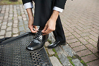 Cropped image of businessman tying his shoe on bench