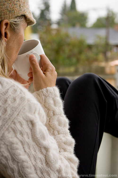 A caucasian woman sits alone on a porch in the morning drinking coffee.