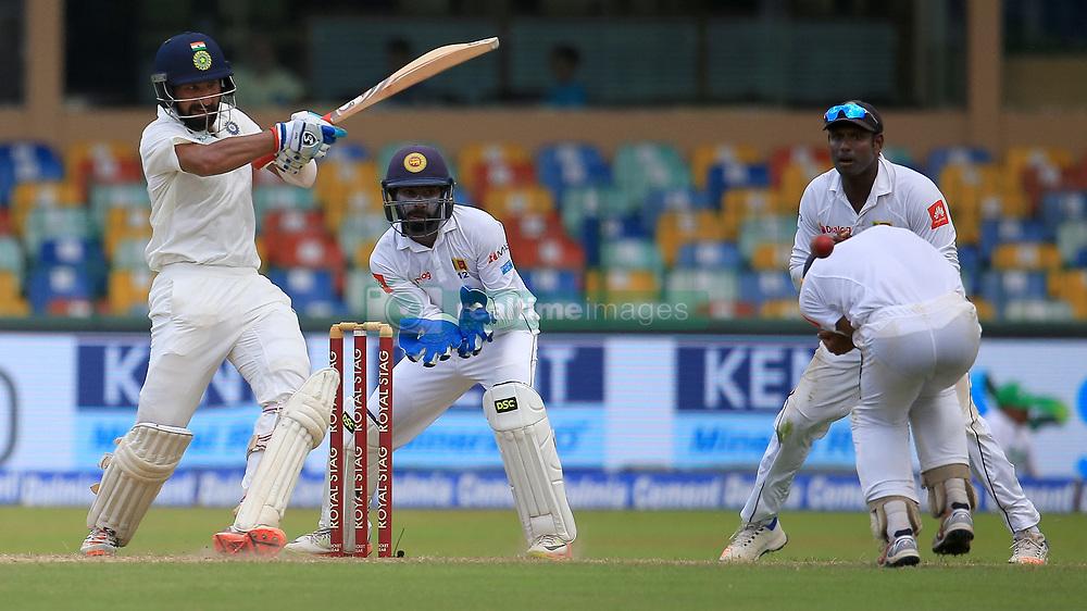 August 3, 2017 - Colombo, Sri Lanka - Indian cricketer Cheteshwar Pujara(L) plays a shot as Sri Lankan cricketer Kusal Mendis reacts during the 1st Day's play in the 2nd Test match between Sri Lanka and India at the SSC international cricket stadium at the capital city of Colombo, Sri Lanka on Thursday 03 August 2017. (Credit Image: © Tharaka Basnayaka/NurPhoto via ZUMA Press)