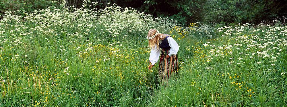 Estonian girl gathering flowers on the wooodland's edge