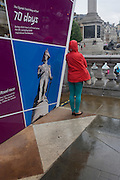 Tourist stands next to a picture of Lord Nelson, the famous British naval commander at a London 2012 Olympic information kiosk in the capital's Trafalgar Square.