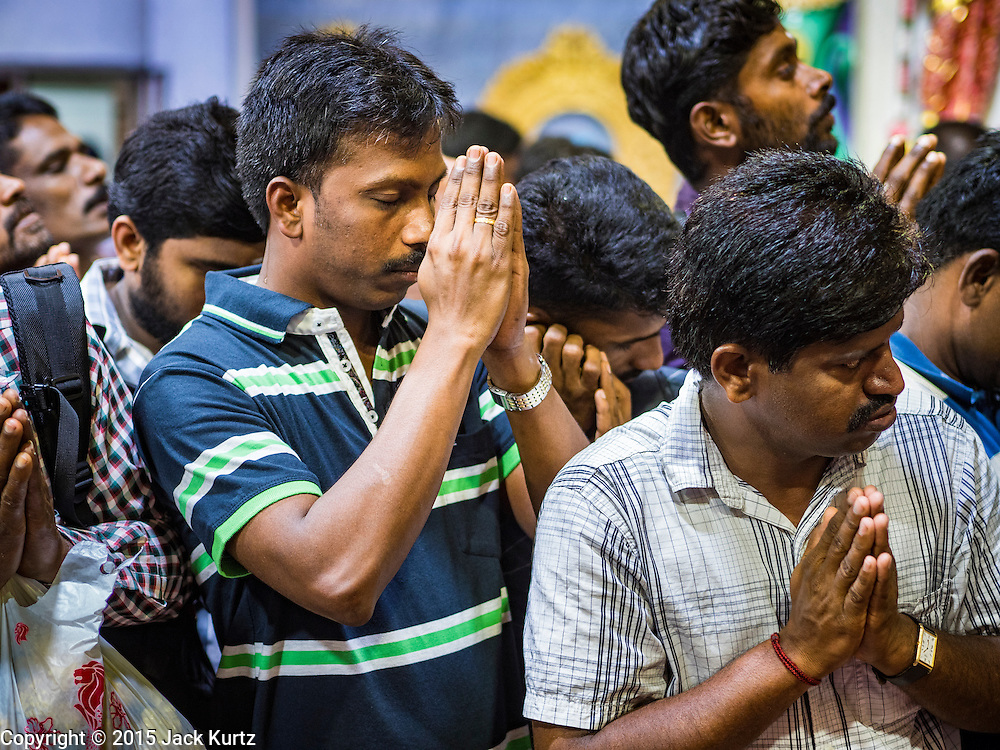 """27 DECEMBER 2015 - SINGAPORE, SINGAPORE:  People pray at Sri Veeramakaliamman Temple in Singapore. Sri Veeramakaliamman Temple in the """"Little India"""" section of Singapore, was one of the first Hindu temples in Singapore and is dedicated to the Goddess Kali, the Hindu """"Destroyer of Evil.""""  It's on Serangoon Road, which at one time was the center of Singapore's Indian community and served Indian immigrants who worked in the cattle trade that was based around Serangoon Road in the 19th century. Now the temple is a popular tourist site.     PHOTO BY JACK KURTZ"""