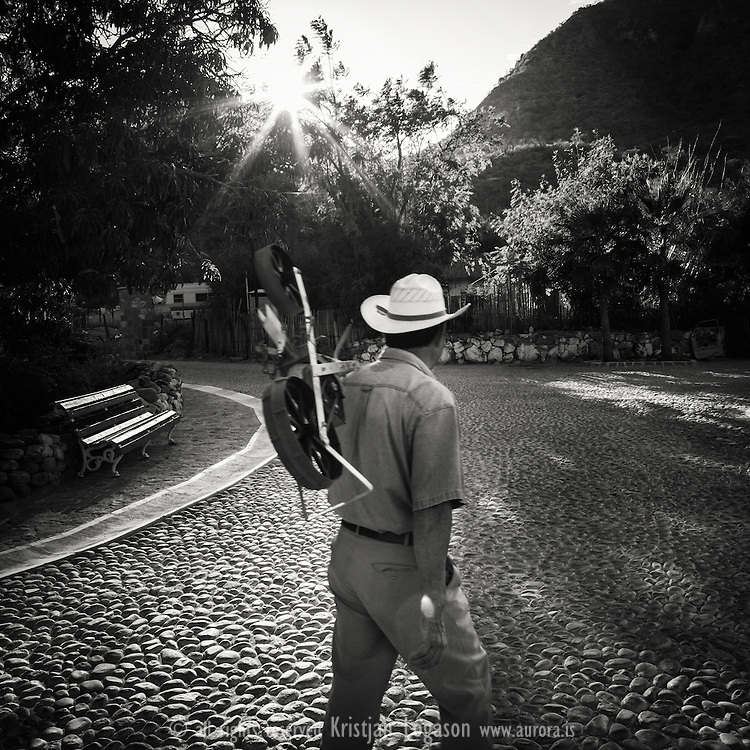 Man walking in the cobblestone streets of San Javier carrying some agricultural devise
