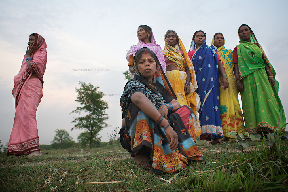 Chandravati (foreground), a Musahar from Naksa Baksa village, that neighbours Charbhariya village, together with other local Musahar women. Chandravati and some of the other women photographed were involved in direct action to ensure that below the poverty line ration cards were distributed to every family in Charbhariya.<br /> <br /> Charbhariya village is home to 87 Musahar families. Despite generations of repression, this community, with the help of local campaigning groups including Action Aid, have achieved some recent successes in the fight for the provision of services. A drainage system is being built in the village as part of the Food For Work Programme and employment has been provided under the National Rural Employment Guarantee Programme. These Government of India schemes are designed to use the rural unemployed to generate productive assets and infrastructure. The campaign for land-rights continues and so far only one of Charbhariya's Musahars has been granted land by the government. The Charbhariya women's self help group is coordinating action to ensure that the local government school has a properly functioning midday-meals programme and that the government funded ICDS (Integrated Child Development Service) is fully operational. Panchayat (or village level) council leader Prabhu Prasad is himself Musahar which provides the community a significant opportunity to demand their rights from the local administration. Direct action by the community recently ensured that below the poverty line ration cards were distributed to every family in Charbhariya.<br /> <br /> The Musahar community are one of India's most impoverished and marginalised groups. They are considered untouchable within the heavily stratified Hindu caste system. Most Musahar people reside in rural districts of Nepal and India's Uttar Pradesh, Madhya Pradesh and Bihar states where they are the victims of ingrained local prejudice and administrative indifference. Literacy levels in the commun