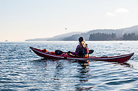 A female sea kayaker watching as a sea plane lands just south of Ganges Harbor, Salt Spring Island, BC, Canada.