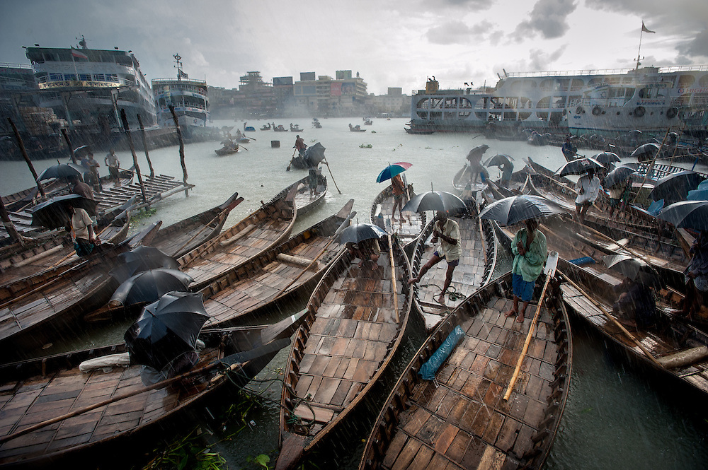 Water taxi drivers take shelter during a rain storm over the Buriganga river in Dhaka, Bangladesh.