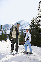 Skiing couple looking over shoulder standing on ski slope back view