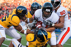 November 7, 2009; Berkeley, CA, USA;  Oregon State Beavers tight end Joe Halahuni (87) is tackled after a pass reception by California Golden Bears linebacker Michael Mohamed (18) and cornerback Brett Johnson (25) during the first quarter at Memorial Stadium.
