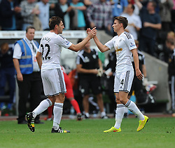 Swansea City's Angel Rangel celebrates the win with Swansea City's Tom Carroll - Photo mandatory by-line: Alex James/JMP - Mobile: 07966 386802 30/08/2014 - SPORT - FOOTBALL - Swansea - Liberty Stadium - Swansea City v West Brom - Barclays Premier League