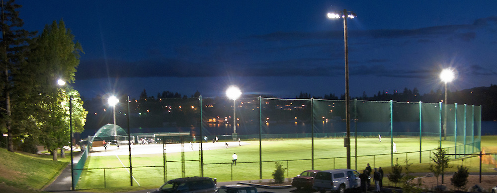 Lights stretch playing time into late evening at Lions Field in Bremerton, WA where a couple local recreation teams play baseball.