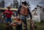 A cowboy walks to the chutes to saddle his ride prior to competing in the broncos during the 101st Falkland Stampede in Falkland, BC. (2019)