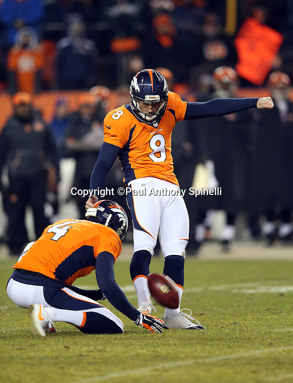 Denver Broncos punter Britton Colquitt (4) holds while Denver Broncos kicker Brandon McManus (8) kicks a field goal good for a 20-17 overtime lead during the 2015 NFL week 16 regular season football game against the Cincinnati Bengals on Monday, Dec. 28, 2015 in Denver. The Broncos won the game in overtime 20-17. (©Paul Anthony Spinelli)