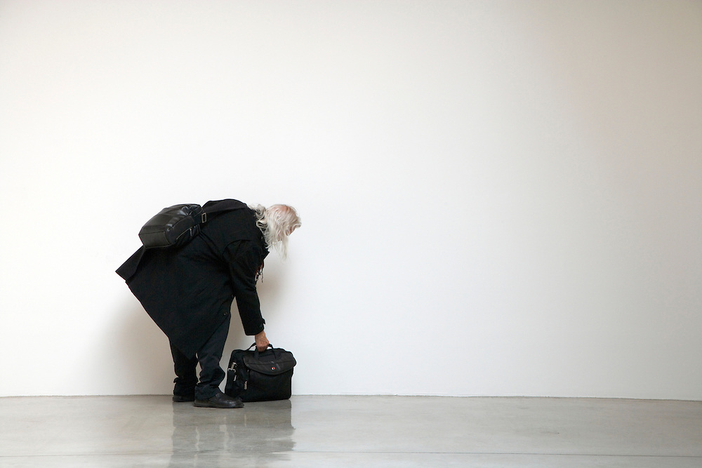 male person picking up his backed briefcase