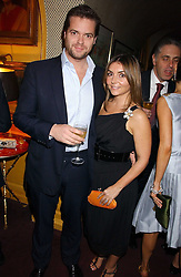 ADRIAN & VASSI HARRIS at a dinner hosted by Stratis & Maria Hatzistefanis at Annabel's, Berkeley Square, London on 24th March 2006 following the christening of their son earlier in the day.<br />