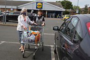 On the Friday May Bank Holiday in the UK and during the UK's Coronavirus pandemic lockdown, two women wearing home-made masks emerge from a branch of Lidl supermarket in Peckham, on 8th May 2020, in London, England.