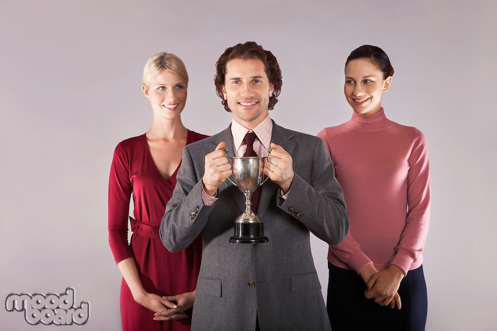 Businessman holding trophy with female colleagues portrait