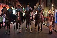 Police on horseback patroilling New Orleans French Quarter.