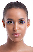 Portrait of beautiful young woman with blue eyeshadow against white background