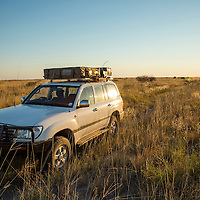 Botswana, Nxai Pan National Park, Land Cruiser with roof tent standing in grass-covered salt pan at dawn