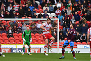 Doncaster Rovers defender Andrew Butler (6) heads ball clear away from Scunthorpe United forward Lee Novak (17)  during the EFL Sky Bet League 1 match between Doncaster Rovers and Scunthorpe United at the Keepmoat Stadium, Doncaster, England on 17 September 2017. Photo by Ian Lyall.