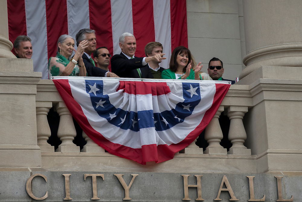 Vice President Mike Pence, center, watches the St. Patrick's Day parade from the balcony at City Hall, Saturday, March 17, 2018, in Savannah, Ga. (AP Photo/Stephen B. Morton)