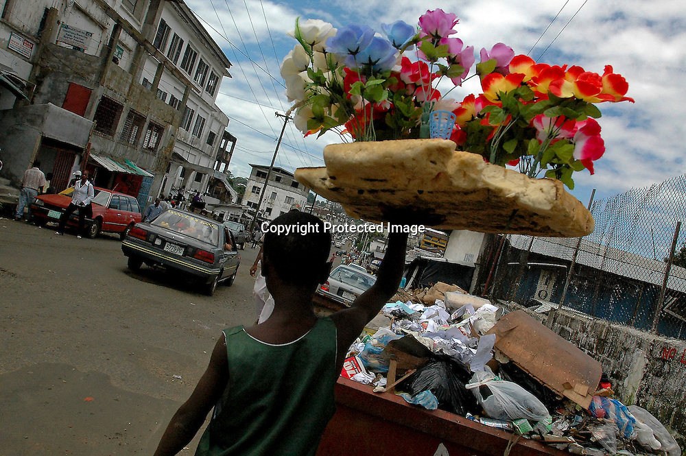 A boy selling plastic flowers makes his way down Carey Street in central Monrovia, Liberia, October 12, 2005.  The first presidential election here in 8 years came off the day before, as yet without any reports of violence or election fraud.