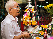 16 OCTOBER 2014 - BANGKOK, THAILAND: A man prays at a shrine to King Chulalongkorn, also known as Rama V in the Flower Market in Bangkok. Chulalongkorn was the fifth king of the Chakri dynasty and is one of the most revered Kings in Thai history. He is credited with leading the drive to modernize Thailand, then Siam, and keeping Siam independent when both British and French colonial authorities were pressing in on Siam.     PHOTO BY JACK KURTZ