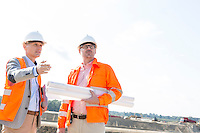 Supervisors with blueprints discussing at construction site against clear sky