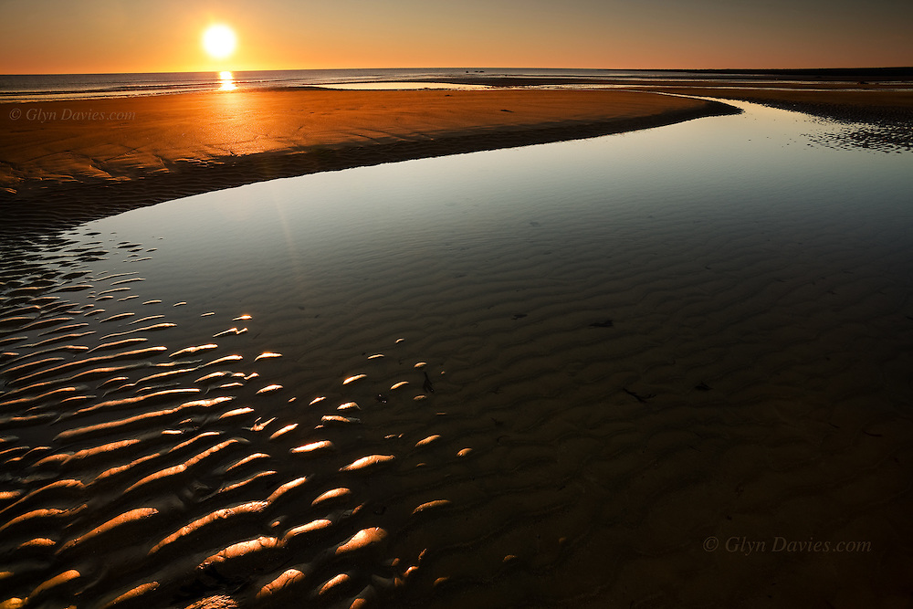 A large tidal pool is left on this sandy beach at Rhosneigr, West Anglesey, Wales, draining into the sea on a windless day as the sun sets in a cloudless sky.