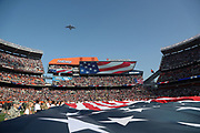 A military transport jet flies over FirstEnergy Stadium during the playing of the National Anthem as members of the U.S. Military wave a large American flag over the field before the Cleveland Browns 2016 NFL week 9 regular season football game against the Dallas Cowboys on Sunday, Nov. 6, 2016 in Cleveland. The Cowboys won the game 35-10. (©Paul Anthony Spinelli)