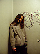A girl standing against a wall covered in tags