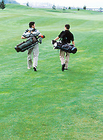 Two men walking down a fairway with their golf clubs.